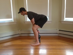 Joe DeLeo performing a kettlebell deadlift on a yoga block.